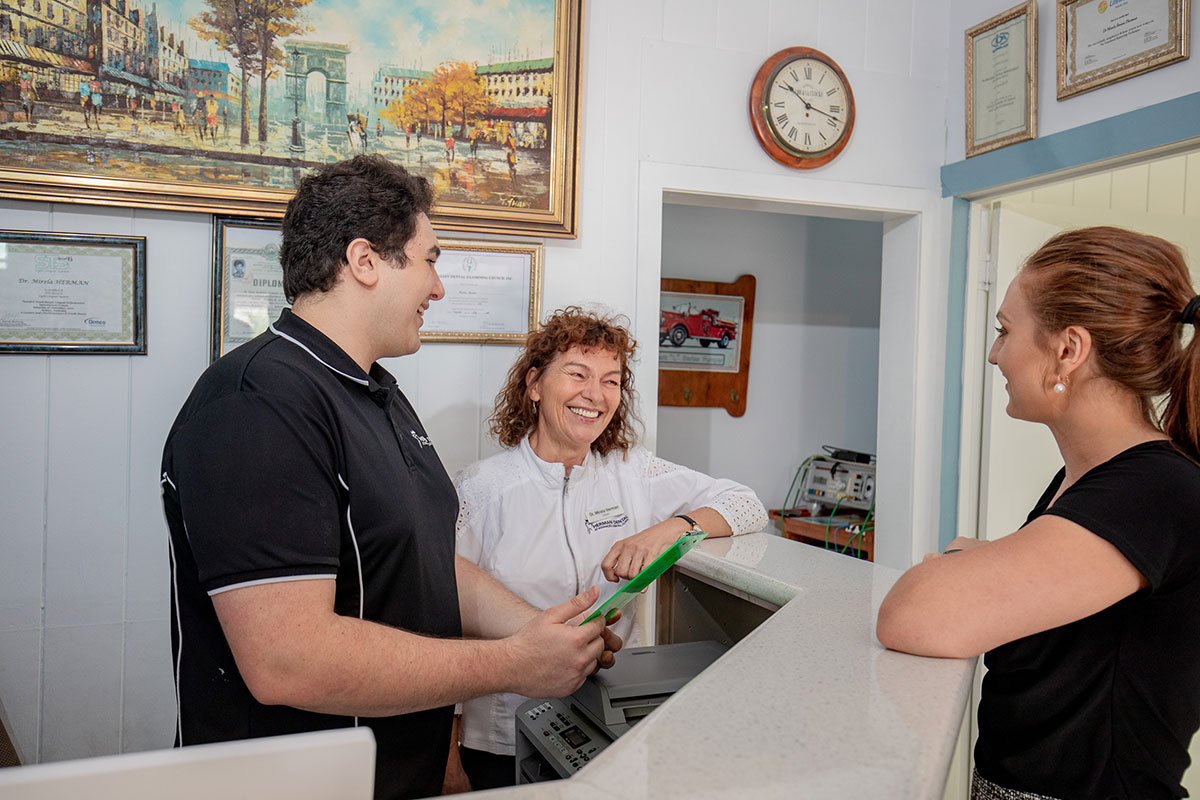 Dentist, receptionist and patient chatting